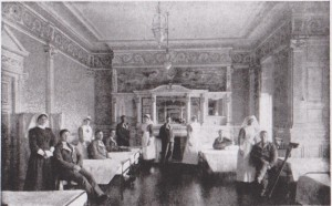 Photograph of nurses and patients in the drawing room of Seafield House being used as a ward in a Red Cross Hospital