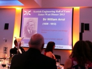 Photograph of presentation at the James Watt Dinner with screen displaying the entry for Sir William Arrol