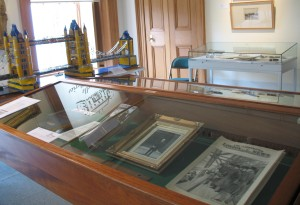 photograph of a display case containing photographs and books of Sir William Arrol with a scale model of Tower Bridge in the background.