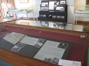 photograph of a display case containing a board with information about Sir William Arrol and in the background another information board and stereoscope with photographs of Arrol bridges.