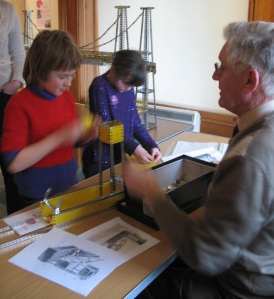 photograph of a boy and girl building sections of a bridge using meccano with help from a meccano expert