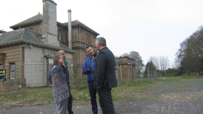 Photograph of interviewer with microphone interviewing 3 people in front of derelict building