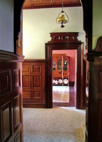 Photograph of a hallway with wooden half-panelled walls looking through a doorway to the dining room beyond.