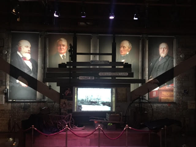 colour photograph showing the 4 portraits on display at Tower Bridge Exhibition.