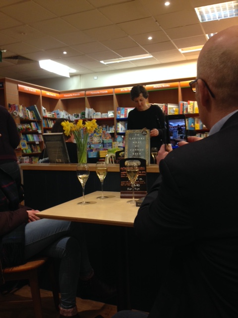 photogrraph of woman in a bookshop reading from a book with others sitting listening and drinking wine.