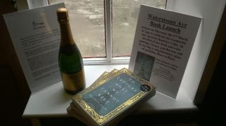 photograph of a bottle of sparkling wine, the book, and display fliers on a window ledge