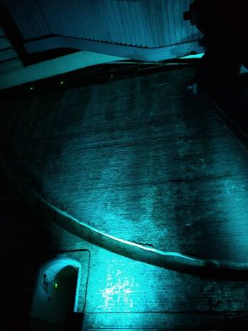Photograph of the side wall of the bascule chamber illuminated in blue showing doorway, steel counterbalance and groove along which the counterbalance moves