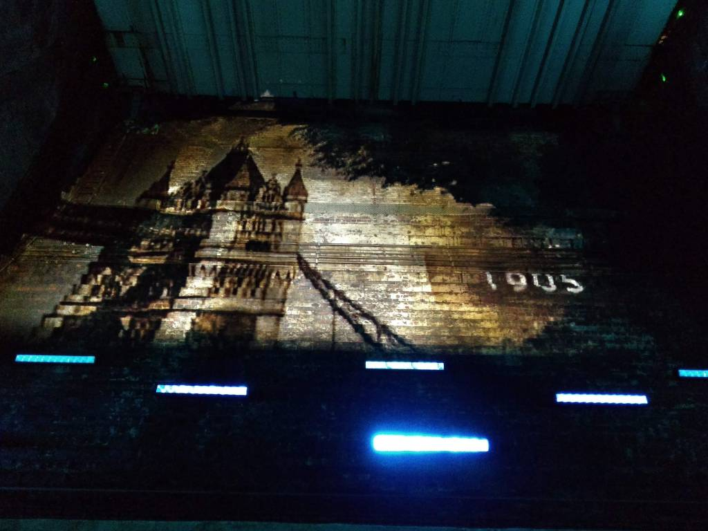 Photograph of a sepia photograph of Tower Bridge projected onto a wall with blue lights below.