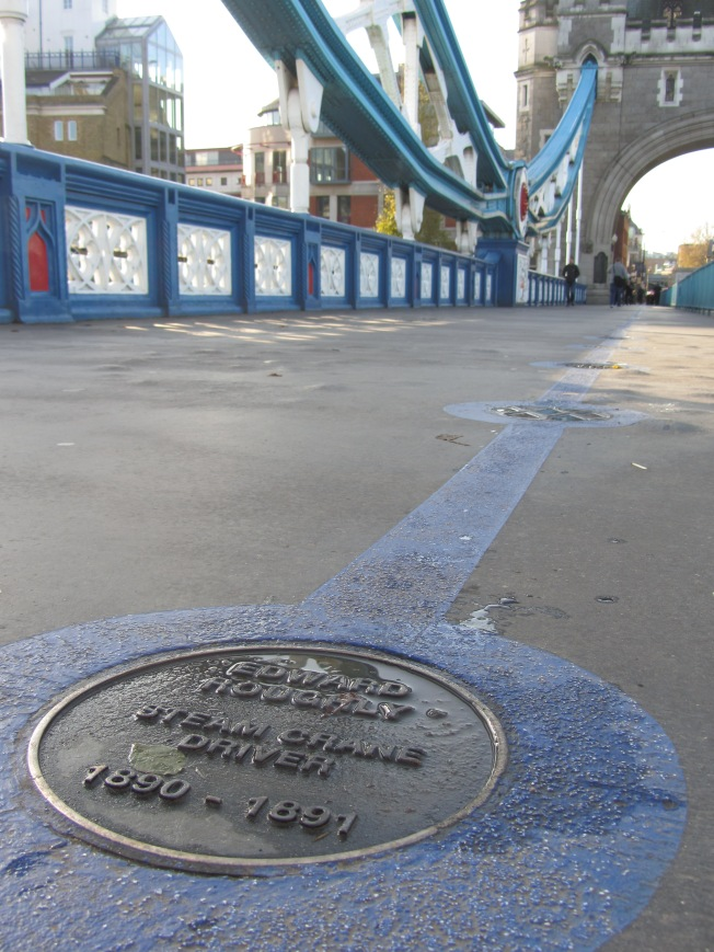 photograph of a brass plaque in a blue painted line leading across the walkway on Tower Bridge