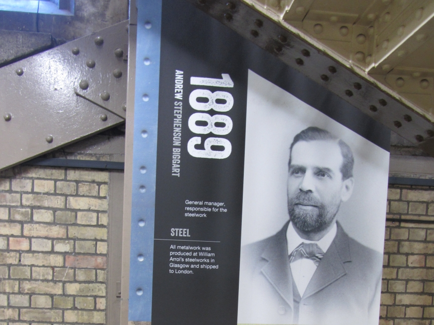 Photograph of banner with date 1889 and photograph of Andrew Stephenson Biggart and paragraph about the metalwork produced at Sir William Arrol's steelworks.