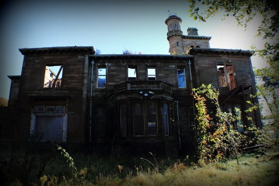 Colour photograph of the derelict building with ground floor windows boarded up and upper windows and roof missing