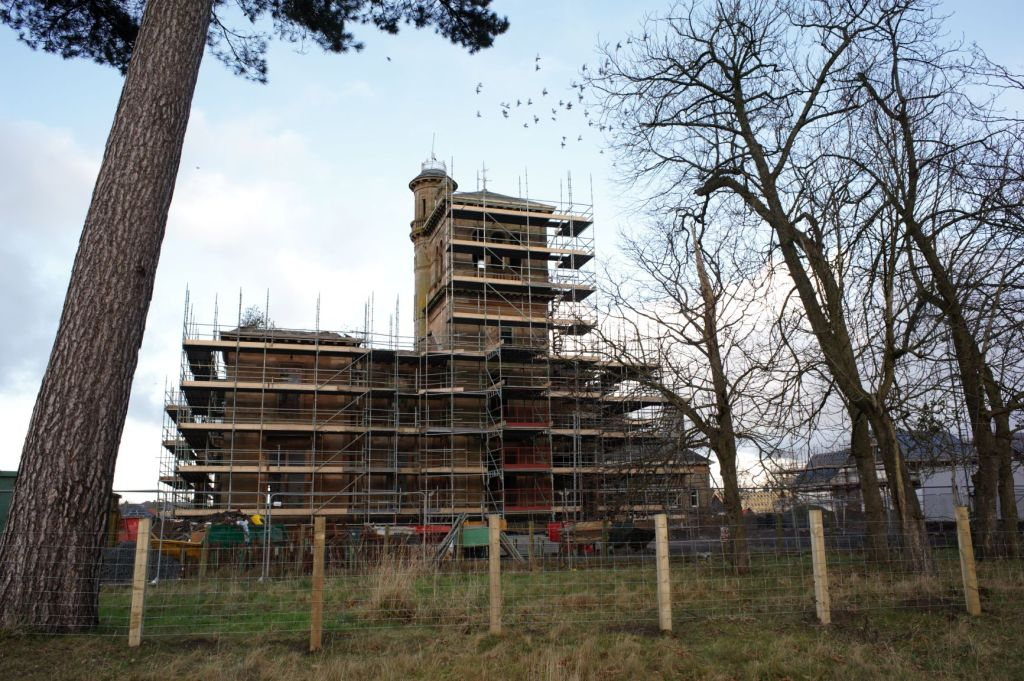 Seafield House from the distance surrounded in scaffolding up to the level of the tower roof. Trees in the foreground and a new build house to the right.