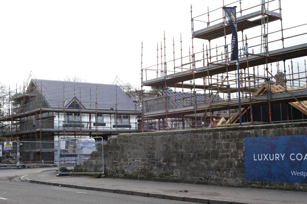 Entrance to the development site showing the gap in existing wall and new build houses on the other side. Two of the houses are roofed and the other is having a roof put on.