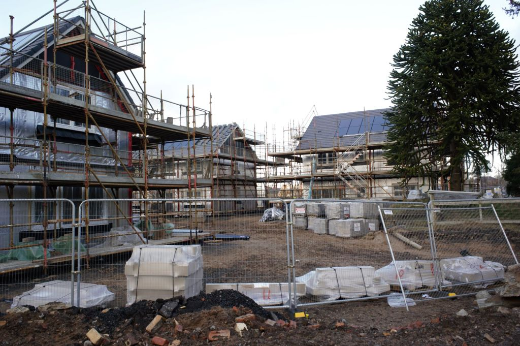 Three new build houses near a monkey puzzle tree. The houses are surrounded in scaffolding. One is having roof tiles put on, another is still to be clad and the third has roof, solar panels and cladding in place.