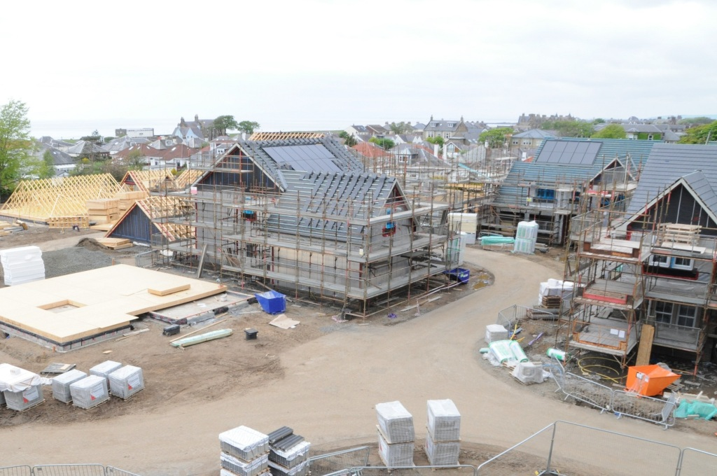 Bird's eye view of three new build houses under construction and foundations for another.