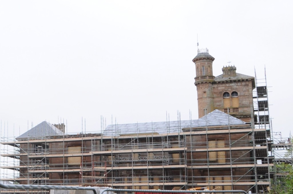 Side elevation of house surrounded by scaffolding and new roofing.
