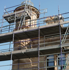 Tower and turret surrounded by scaffolding and showing new windows installed